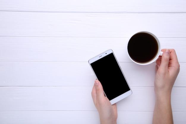 Mãos fêmeas que guardam a xícara de café e o smartphone no fundo de madeira branco.
