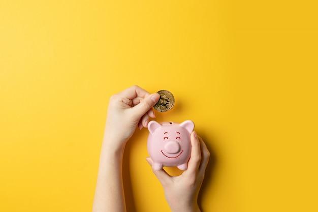 Mãos fêmeas que guardam o mealheiro piggy e que põem o dinheiro do bitcoin no banco piggy.
