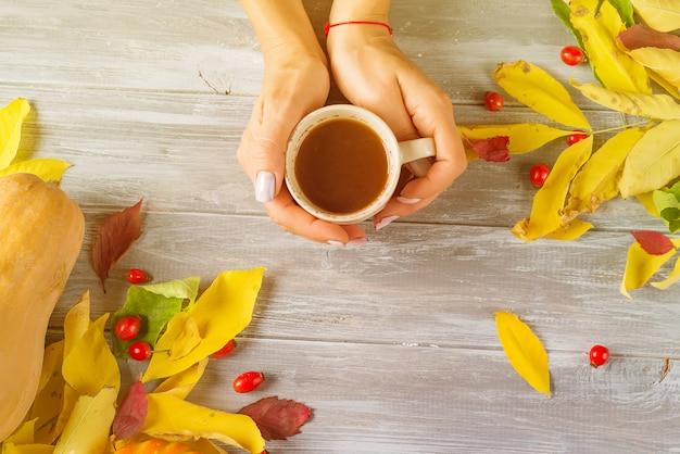 Mãos fêmeas que guardam uma xícara de café em um fundo de madeira cinzento com espaço da cópia. vista do topo