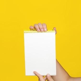 Mãos fêmeas que mantêm aberto um bloco de notas vazio para notas na parede amarela. em tons.