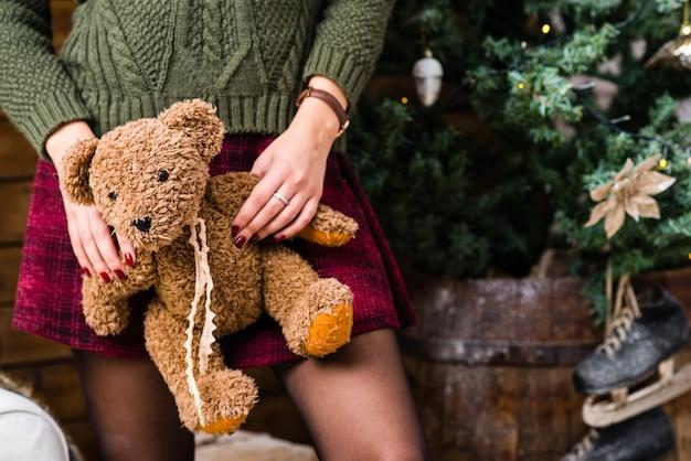 Mãos fêmeas que prendem um urso de peluche bonito. presente de natal.