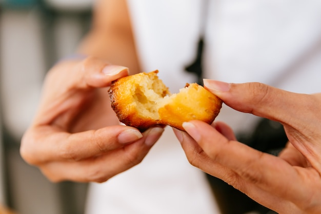 Mãos fêmeas que rasgam canelés cozido fresco.