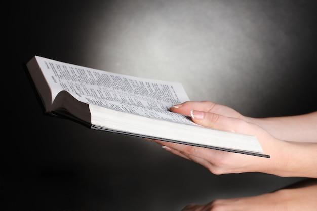 Mãos femininas abertas na bíblia sagrada russa em um fundo preto