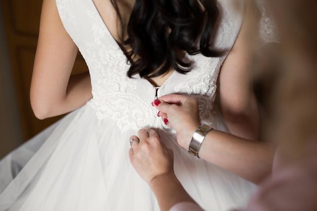 Mãos femininas abotoam o vestido de casamento para a noiva com um penteado bonito
