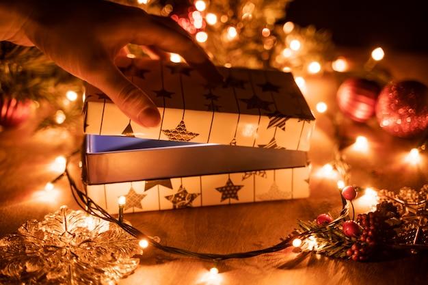 Mãos femininas, abrindo a caixa de presente de natal acima da mesa de madeira.