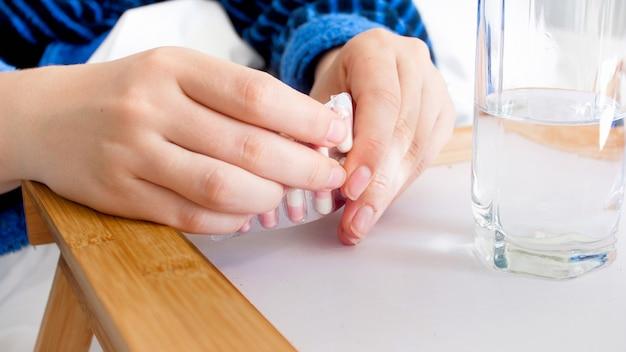 Mãos femininas abrindo comprimidos.