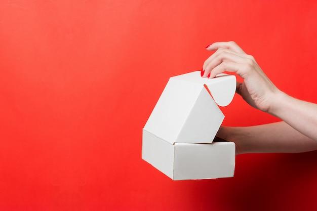 Mãos femininas abrir caixa branca sobre fundo vermelho