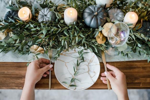 Mãos femininas acima configuração de mesa de outono com abóboras. talheres assustadores de halloween ou ação de graças em fundo escuro de madeira