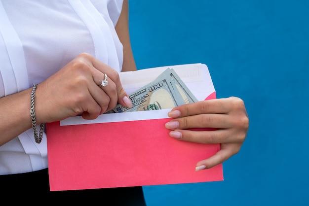 Mãos femininas algemadas, segurando um envelope com dólares. o conceito de corrupção e suborno