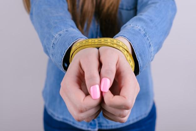 Mãos femininas amarradas com fita métrica isolado fundo cinza