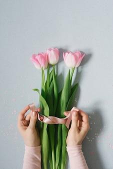 Mãos femininas amarram um laço de fita de cetim em um buquê simples de tulipas rosa frescas