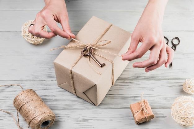 Mãos femininas amarrar o cordão no presente embrulhado na mesa de madeira