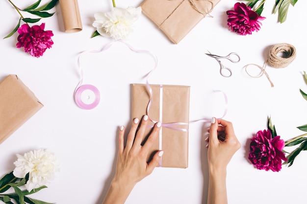 Mãos femininas amarrar uma fita no presente para umas férias na mesa branca