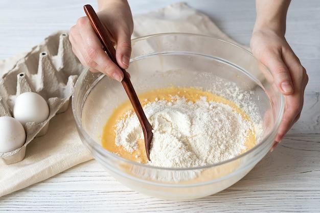 Mãos femininas amassando massa de muffin, receita de panificação caseira