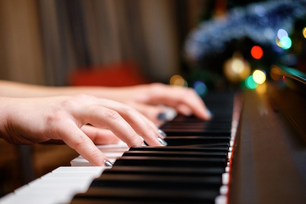 Mãos femininas ao piano, close-up, belo bokeh ao fundo