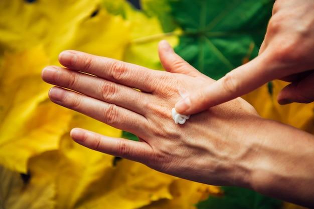 Mãos femininas aplicando creme cosmético hidratante, close-up