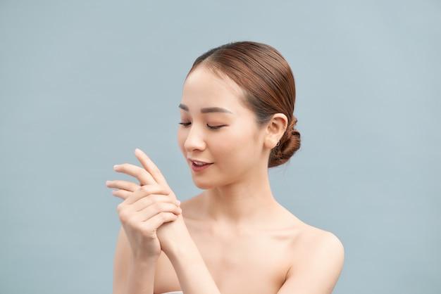 Mãos femininas aplicando creme para as mãos