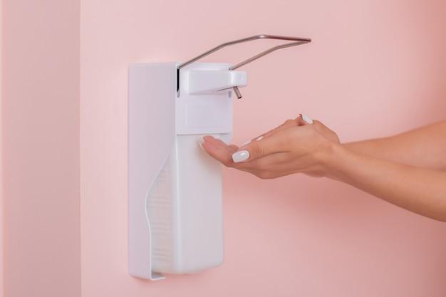 Mãos femininas aplicando sabonete líquido do distribuidor