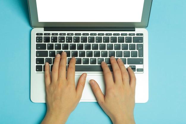 Mãos femininas atrás de um laptop. mãos femininas trabalhando em um teclado de computador