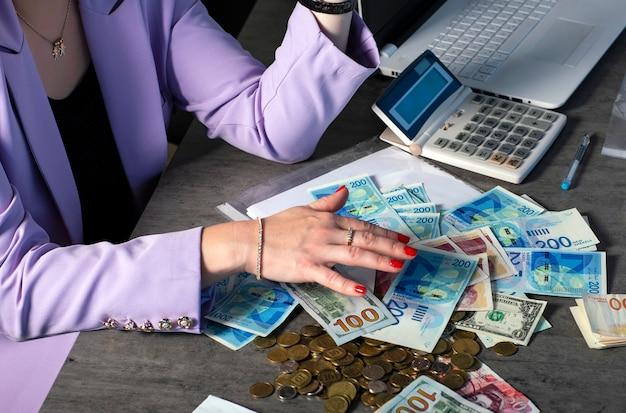 Mãos femininas bem cuidadas com esmalte vermelho pegam uma pilha de dinheiro. dólares, libras esterlinas e novas notas de siclos na mesa. conceito de sucesso, ganância e corrupção, desejo por dinheiro