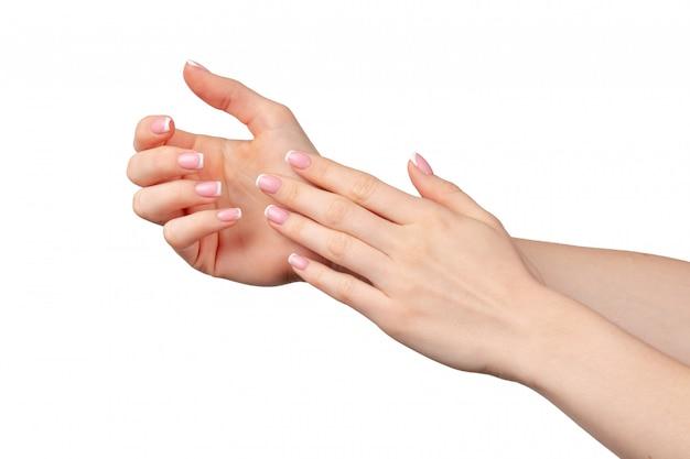 Mãos femininas bem cuidadas com manicure na parede branca