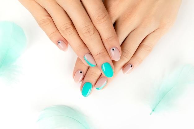 Mãos femininas bem cuidadas com um design moderno e brilhante em branco
