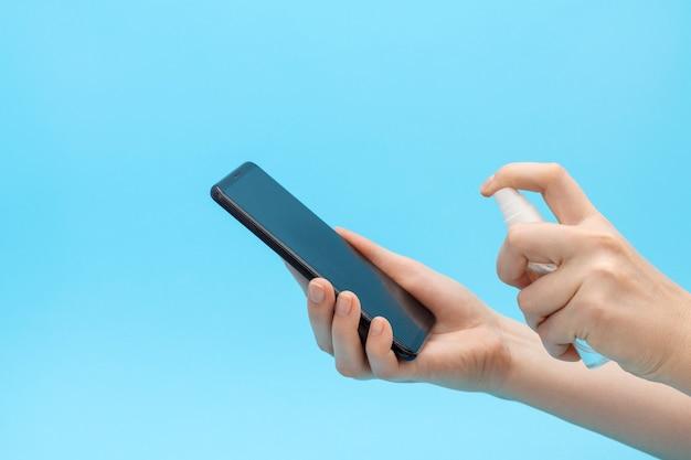 Mãos femininas borrifam desinfetante no celular