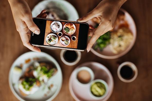Mãos femininas bronzeadas segurando um smartphone e tirando fotos do prato com a refeição