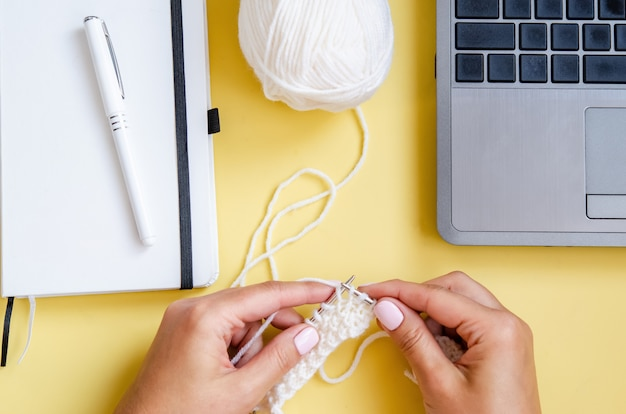 Mãos femininas close-up de malha com agulhas de tricô de lã de fios naturais de cor branca