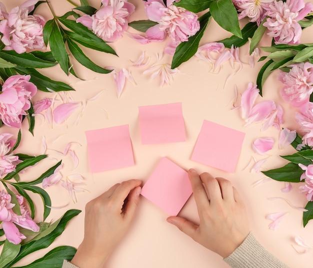 Mãos femininas cola adesivos de papel rosa vazio no fundo com peônias florescendo