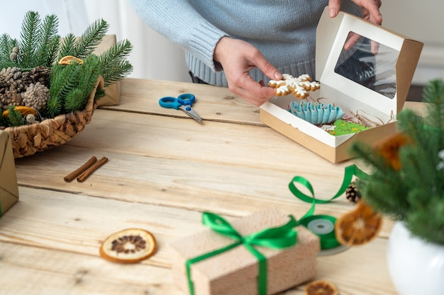 Mãos femininas colocam biscoitos em uma caixa