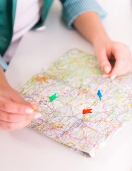 Mãos femininas colocar bandeiras no mapa.