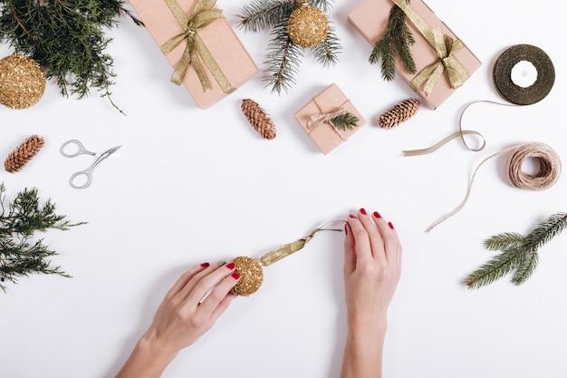Mãos femininas colocar bola de natal amarela em uma mesa branca com abeto de filial, presente, fita, corda e tesoura