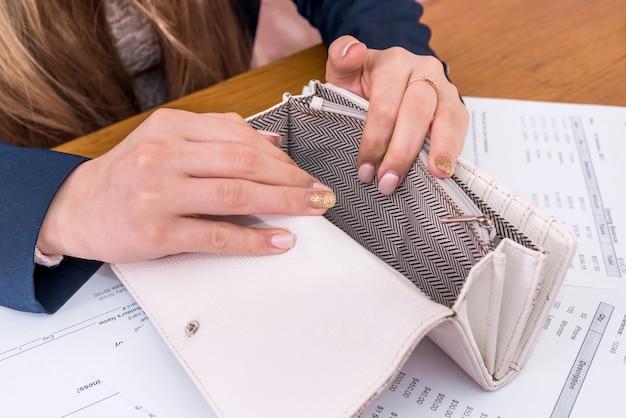 Mãos femininas com a bolsa vazia e pedidos de compra