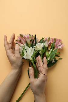 Mãos femininas com anéis e flores de alstroemeria em fundo bege