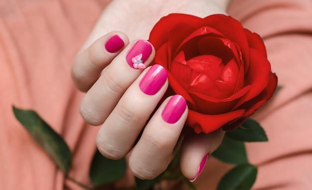 Mãos femininas com arte de unha rosa.
