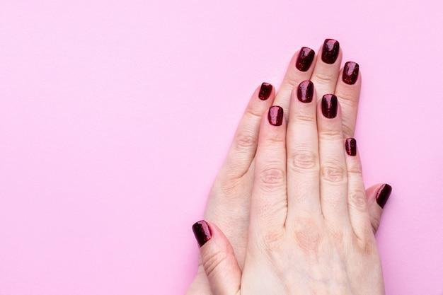 Mãos femininas com bela manicure - unhas brilhantes de vermelho escuro na parede rosa com espaço de cópia.