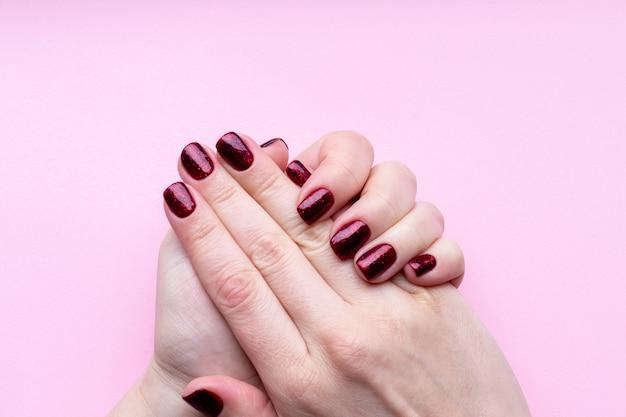 Mãos femininas com bela manicure - unhas brilhantes de vermelho escuro na parede rosa.