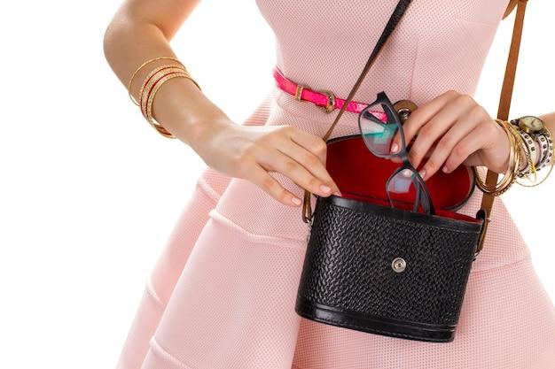 Mãos femininas com bolsa preta. abra a bolsa e os óculos. vestido salmão e bolsa vintage. estojo para acessórios.