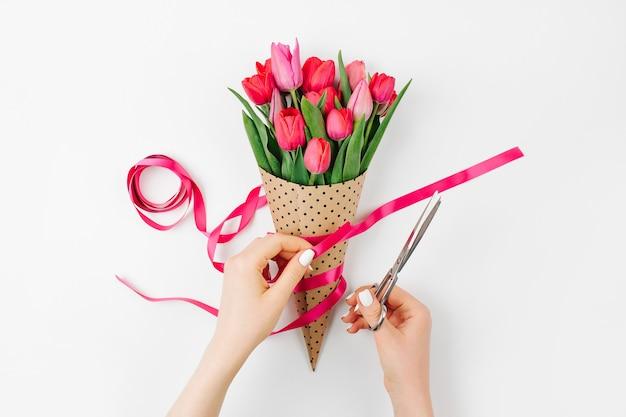Mãos femininas com buquê de tulipas. lindas flores rosa primavera.
