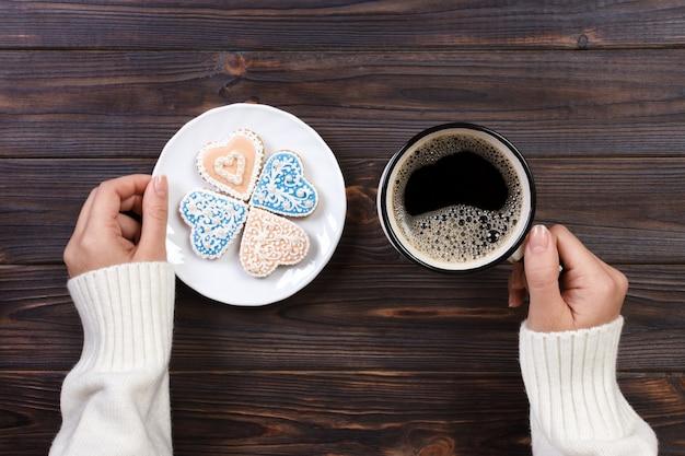 Mãos femininas com café e biscoitos em forma de coração na mesa de madeira, vista superior