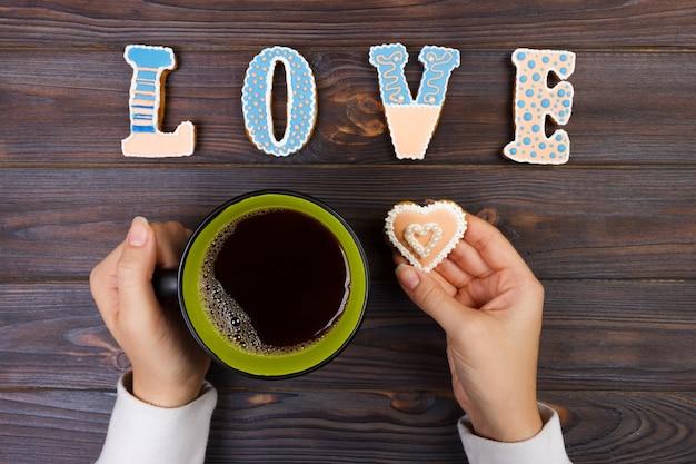 Mãos femininas com café e biscoitos em forma de coração na mesa de madeira