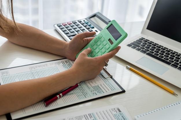 Mãos femininas com calculadora acima do formulário fiscal de 1.040 close-up