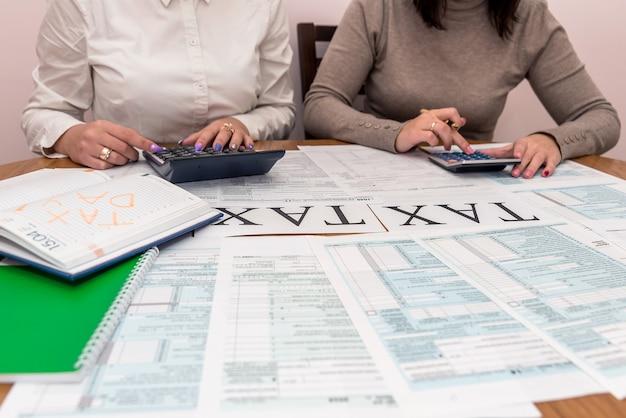 Mãos femininas com calculadora e formulário 1040