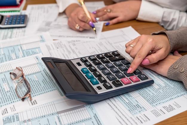 Mãos femininas com calculadora no formulário fiscal 1040