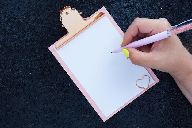 Mãos femininas com caneta de manicure amarelo brilhante escreve na área de transferência.