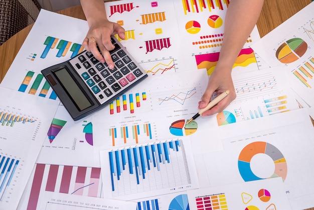 Mãos femininas com caneta e calculadora em gráficos de negócios