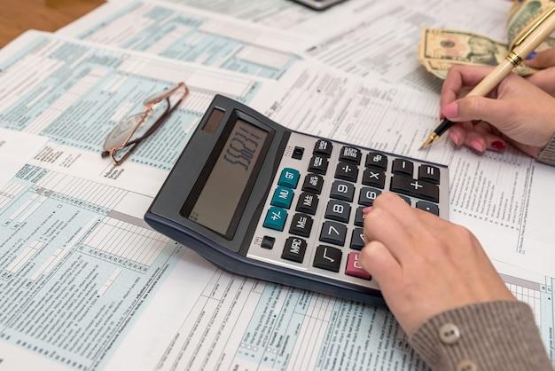 Mãos femininas com caneta e calculadora no formulário 1040