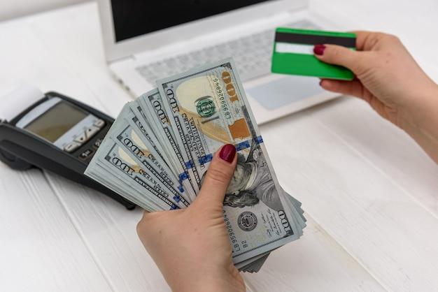 Mãos femininas com cartão de crédito e dólares
