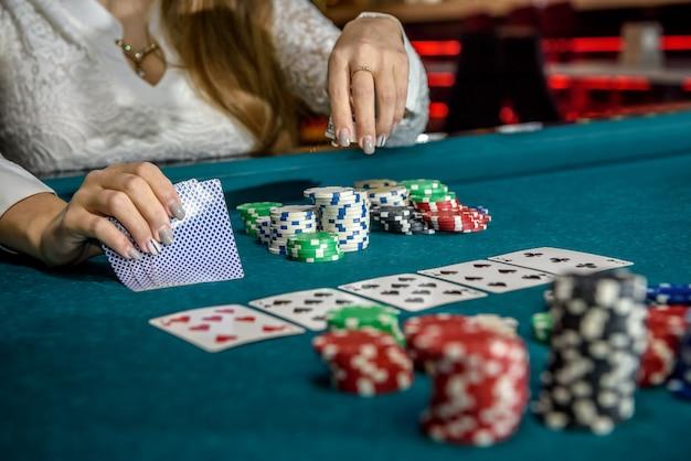 Mãos femininas com cartas de jogar e fichas de pôquer